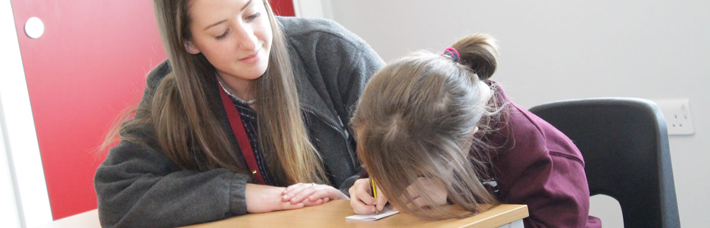 A teacher working with a pupil